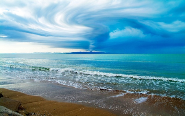 swirling-clouds-above-the-ocean-beach-wallpaper-3111